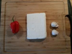 Foto af en Habanero-chili, en blok græsk feta og to fed hvidløg på et skærebræt