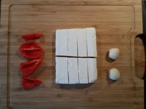 Foto af en habanero delt i fire, en blok feta delt i otte og to fed hvidløg på et skærebræt
